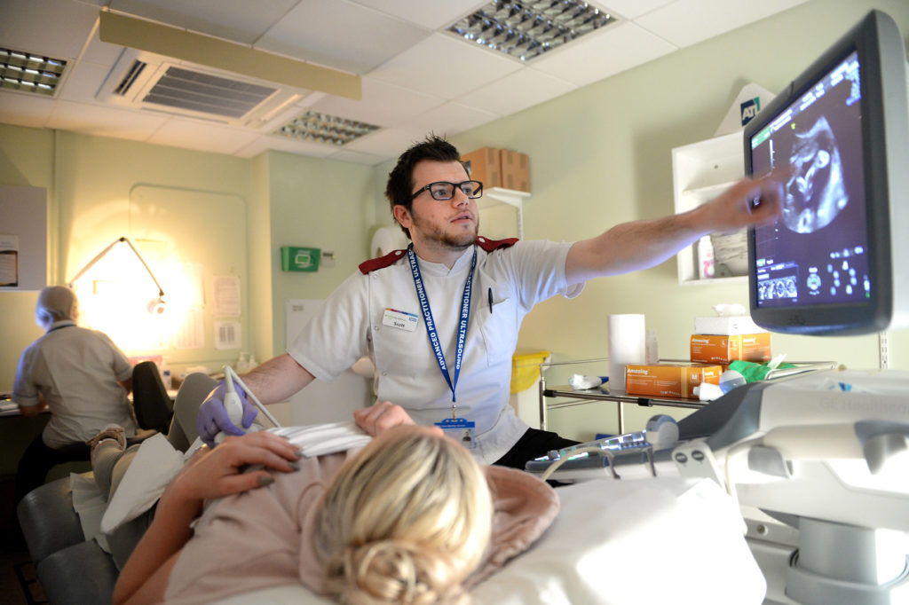 A consultant performing a scan on a patient