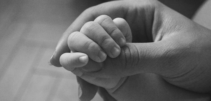 Generic black and white photograph of an adult hand holding a baby's hand