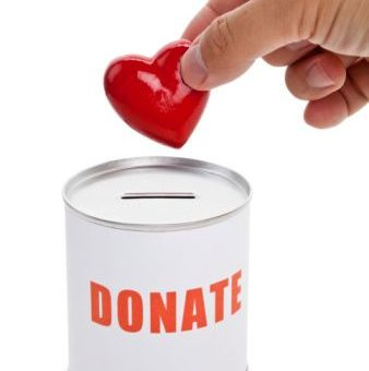 Generic image of a donation box. A hand is depositing a red heart-shaped token