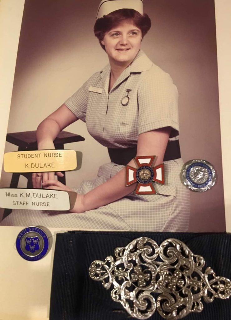 Photograph of Karen Moss with her name badges and nurse's buckle