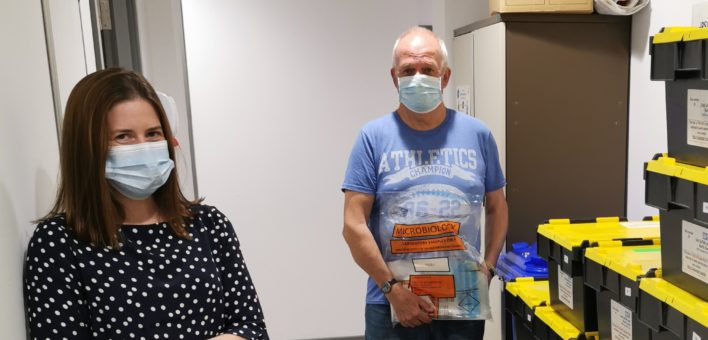 Photograph of Volunteers Claire Rodie and Barry Wellham packing COVID-19 test kits